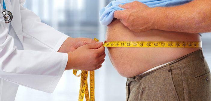 врач измеряет объем талии у мужчины